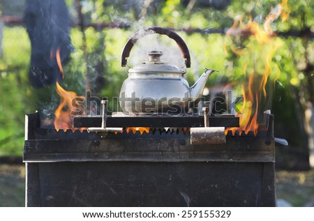 Kettle boils over charcoal - stock photo