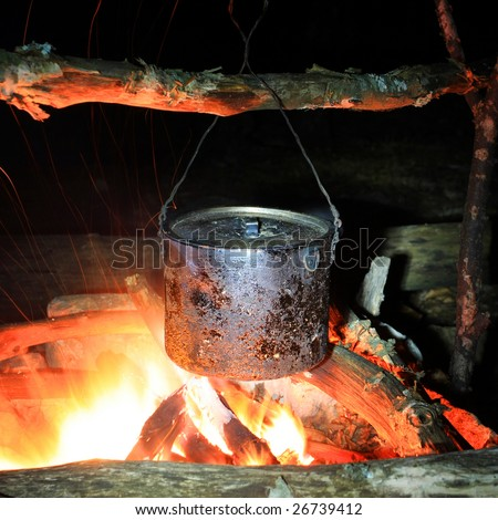 Kettle on hot fire in the tourist camping - stock photo