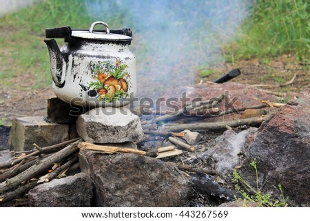 Kettle over burning campfire - stock photo