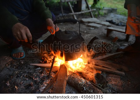 Kettle pot on fire for boiling the water with hand