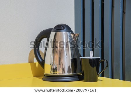 Kettle with coffee on a yellow table. - stock photo