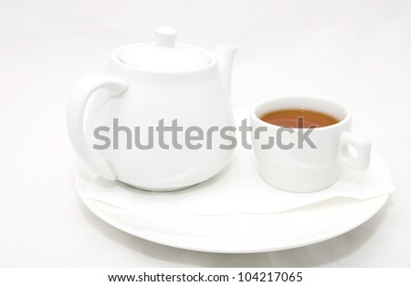Kettle with tea and a mug on a white background