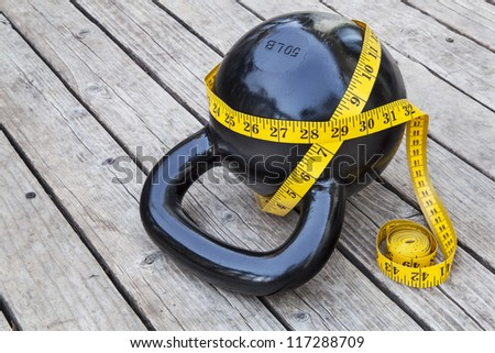 kettlebell and measuring tape on wooden deck - fitness and exercise concept - stock photo