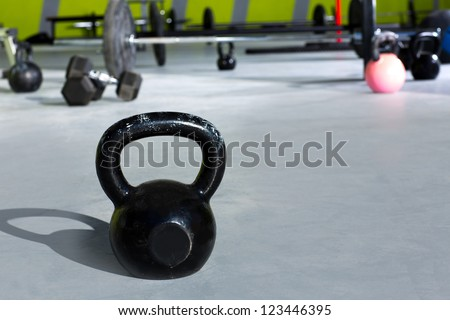 Kettlebell at gym with lifting bars in background - stock photo