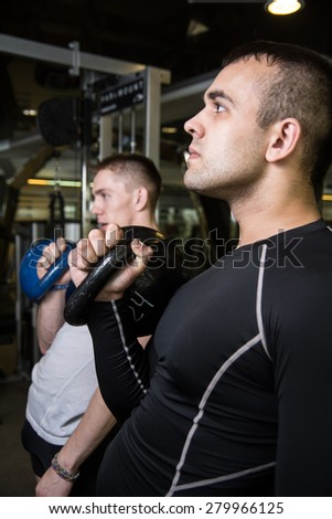 Kettlebell swing training of two young men in the gym. Young men trained muscles