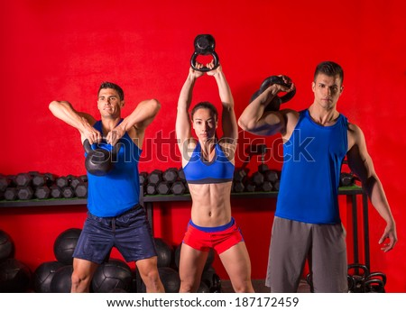 Kettlebell swing workout training group at gym with red wall - stock photo