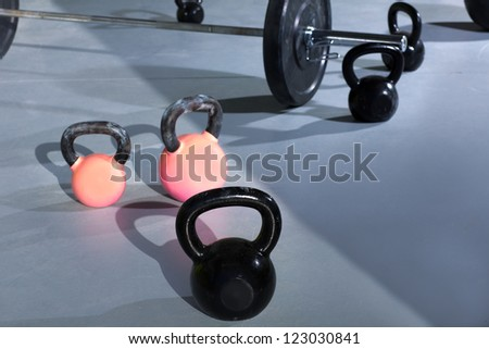 Kettlebells at fitness gym with lifting bar in background - stock photo