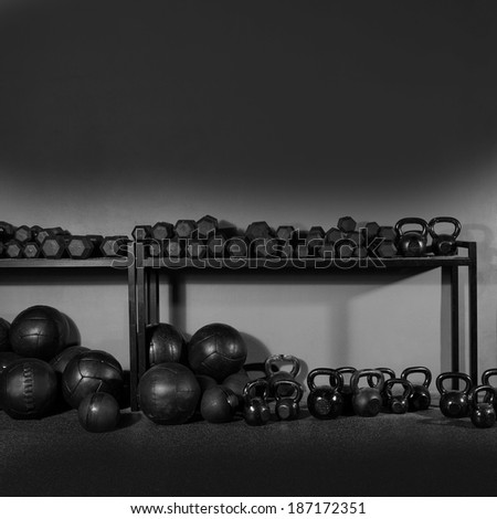 Kettlebells dumbbells and weighted slam balls weight training equipment at gym - stock photo