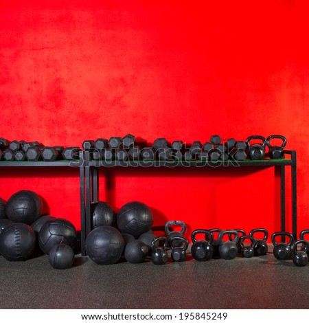 Kettlebells dumbbells and weighted slam balls weight training equipment at gym red wall - stock photo