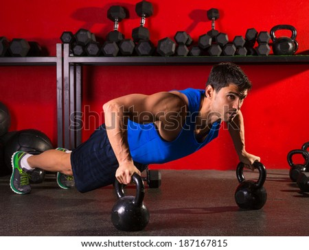 Kettlebells push-up man strength pushup exercise workout at gym - stock photo
