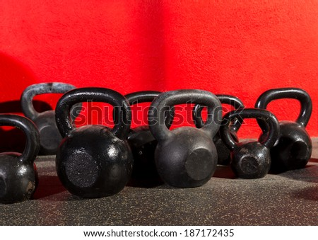 Kettlebells weights in a workout gym in red background - stock photo