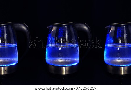 Kettles with blue led lights in dark background - stock photo