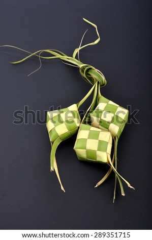 Ketupat (Rice Dumpling) On Black Background. Ketupat is a natural rice casing made from young coconut leaves for cooking rice during eid Mubarak  - stock photo