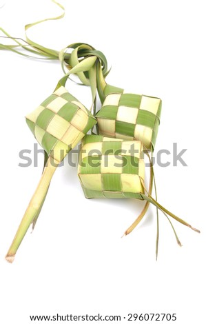 Ketupat (Rice Dumpling) On Rice Background. Ketupat is a natural rice casing made from young coconut leaves for cooking rice during eid Mubarak  - stock photo