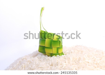 Ketupats, a natural rice casing made from young coconut leaves for cooking rice on rice grain over white background - stock photo