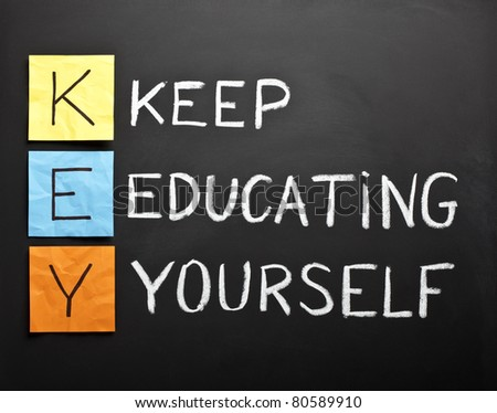 KEY acronym - KEEP EDUCATING YOURSELF. Educational concept with different color sticky notes and white chalk handwriting on a blackboard. - stock photo