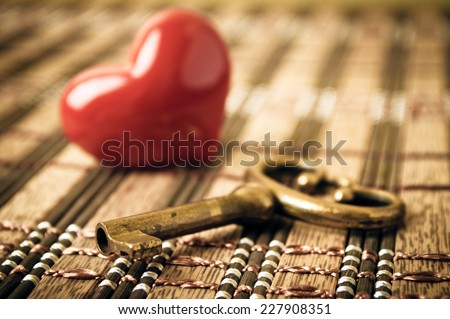 Key and heart with focus on the key - stock photo
