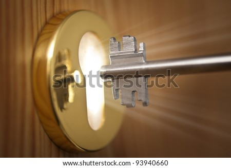 Key and keyhole with light coming from it - stock photo