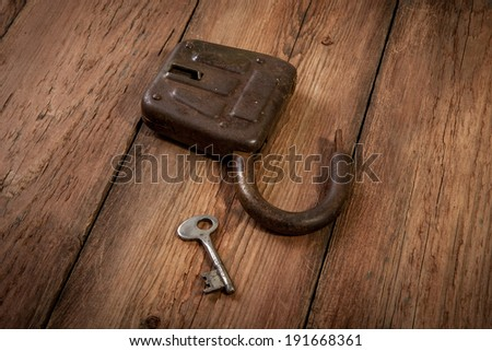 Key and rusty lock on vintage wooden background