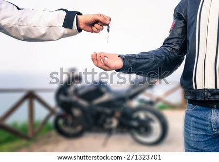 key exchange. Motorcycle concept. friends exchanging the bike key.  - stock photo