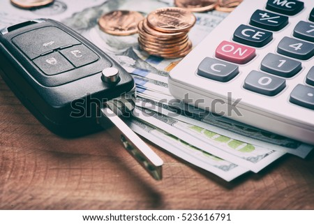 Key from the car and calculator on money. US currency
