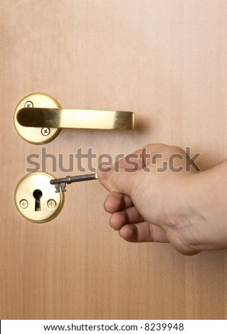 Key in a hand. Attempt to open a door - stock photo