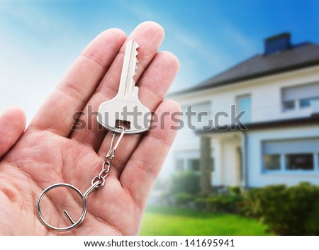 Key in hand against new house - stock photo