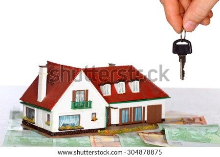 key in hand and symbolic house with money - stock photo