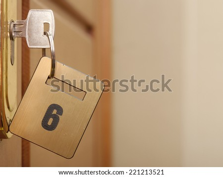 key in keyhole with numbered label  - stock photo