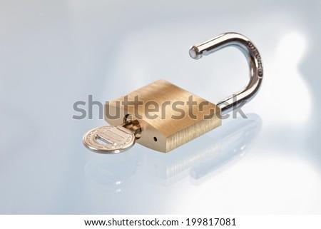 Key in padlock, close-up - stock photo