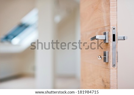 Key in the keyhole of the wooden door - stock photo