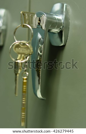 Key insert and hold in metallic knob on brown door horizontal - stock photo