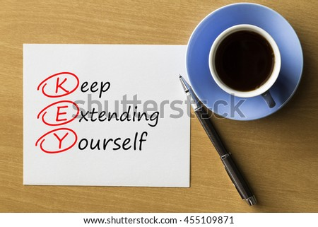 KEY Keep extending yourself - handwriting on paper with cup of coffee and pen, acronym business concept