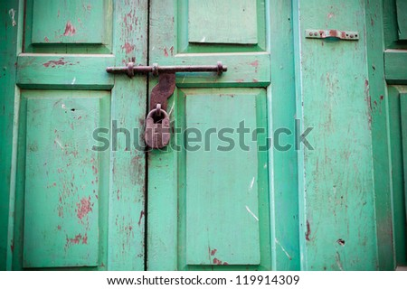 Key lock on green wooden wall - stock photo