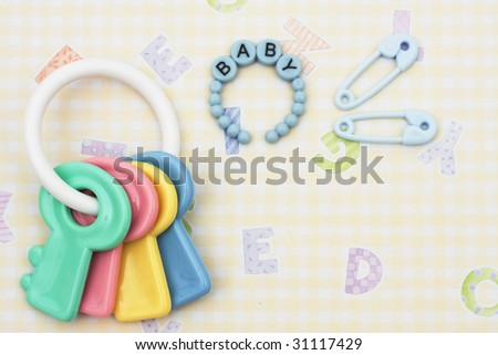 Key shaped baby rattle with pink bracelet and diaper pins sitting on a yellow alphabet background, baby rattle - stock photo