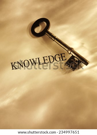 Key to knowledge on a Paper Background with Gold Lighting and Copy Space