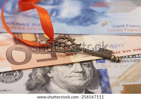 Key To Success With Red Bow on American dollars, European euro,Swiss franc currency - stock photo