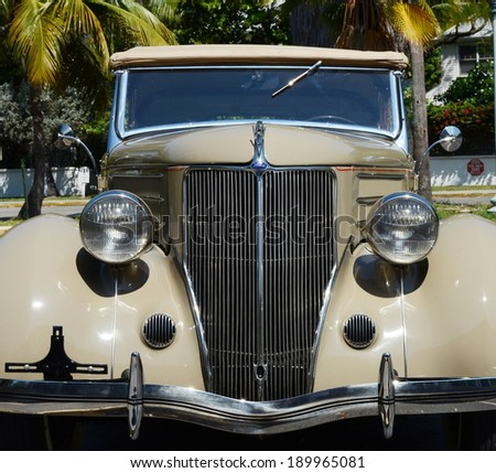 KEY WEST, FL-APRIL 27:  Closeup frontal view of a beige 1936 Ford Touring Phaeton Convertible Sedan in Key West, Florida on April 27, 2014. - stock photo