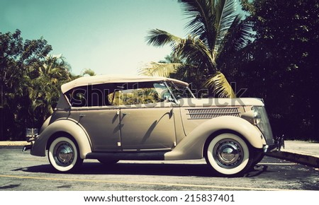 KEY WEST, FL-APRIL 27: Passenger side view of a beige 1936 Ford Touring Phaeton Convertible Sedan in Key West, Florida on April 27, 2014, with instagram-type filter applied for vintage effect.  - stock photo