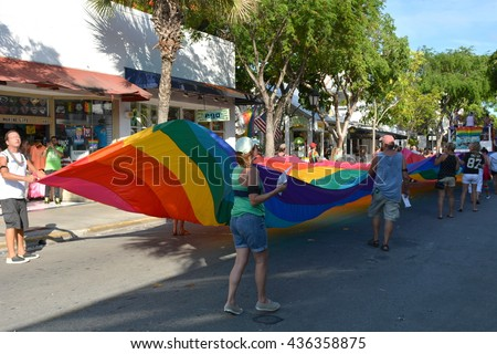 KEY WEST, FL-JUNE 12: People marching in the 2016 Key West Gay Pride parade carry a rainbow gay flag banner on Sunday, June 12, 2016, in Key West, Florida.