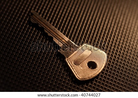 Key with a copyspace on black texture background - stock photo