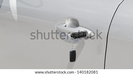 Key with alarm system in the car door outdoors