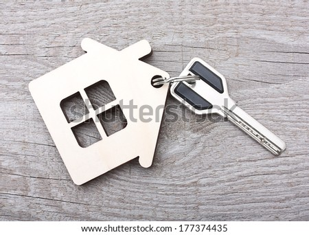 Key with house on wooden desk - stock photo