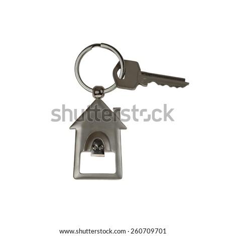 Key with house shape metallic trinket isolated on white background - real estate ownership concept - stock photo