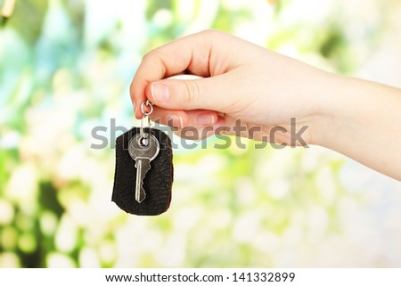 Key with leather trinket in hand on bright background