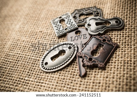 Key with love written on it surrounded by keyholes. - stock photo