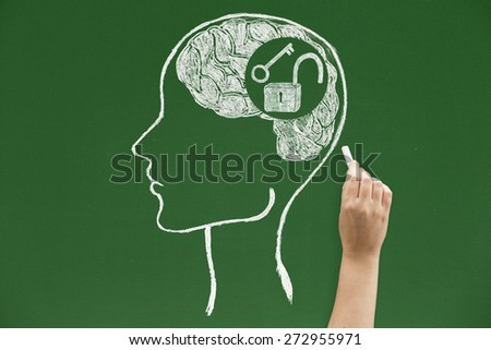 Key with open padlock inside brain sketched on blackboard Concepts and ideas on blackboards - stock photo