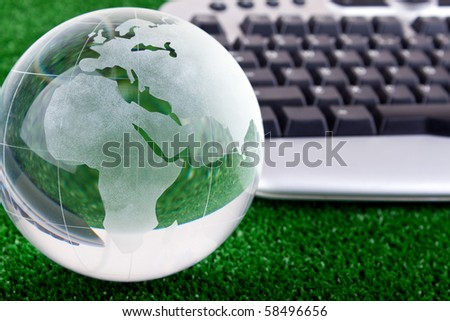 keyboard and glass globe on green grass - stock photo