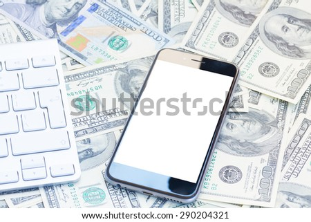 keyboard and modern phone  on money background, copy space on screen - stock photo