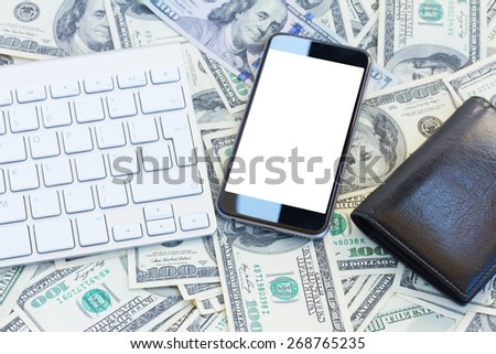 keyboard and modern phone  with white copy space on screen on money background - stock photo